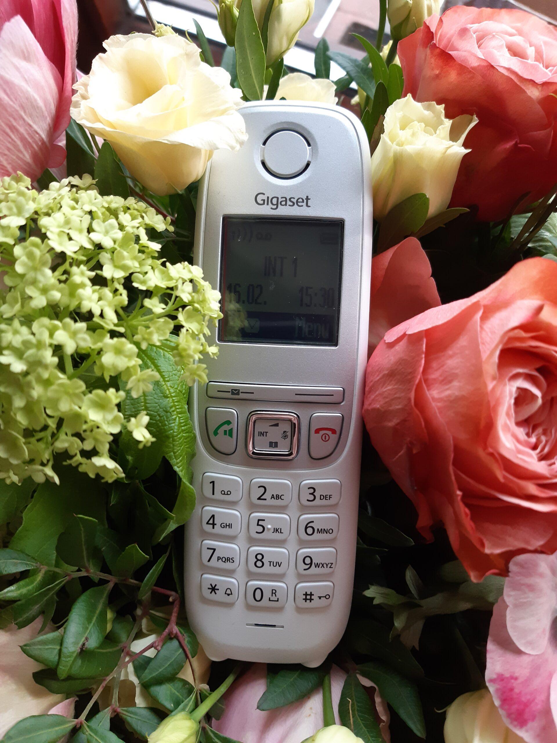 Foto eines Telefons, das in einen Blumenstrauß eingebettet ist