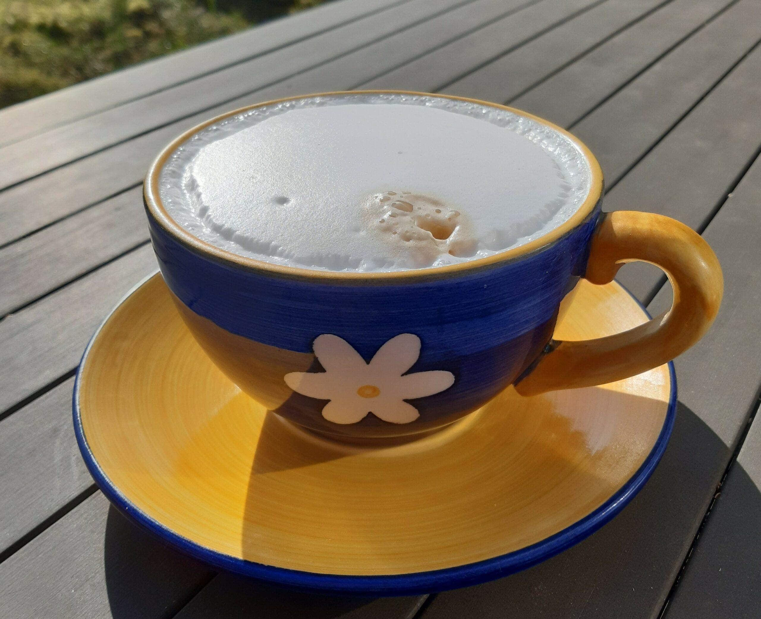 Foto Milchkaffee mit in einer großen blauen Tasse mit weißer Margarite auf gelber Untertasse in der Sonne auf einem Gartentisch in Oldenburg