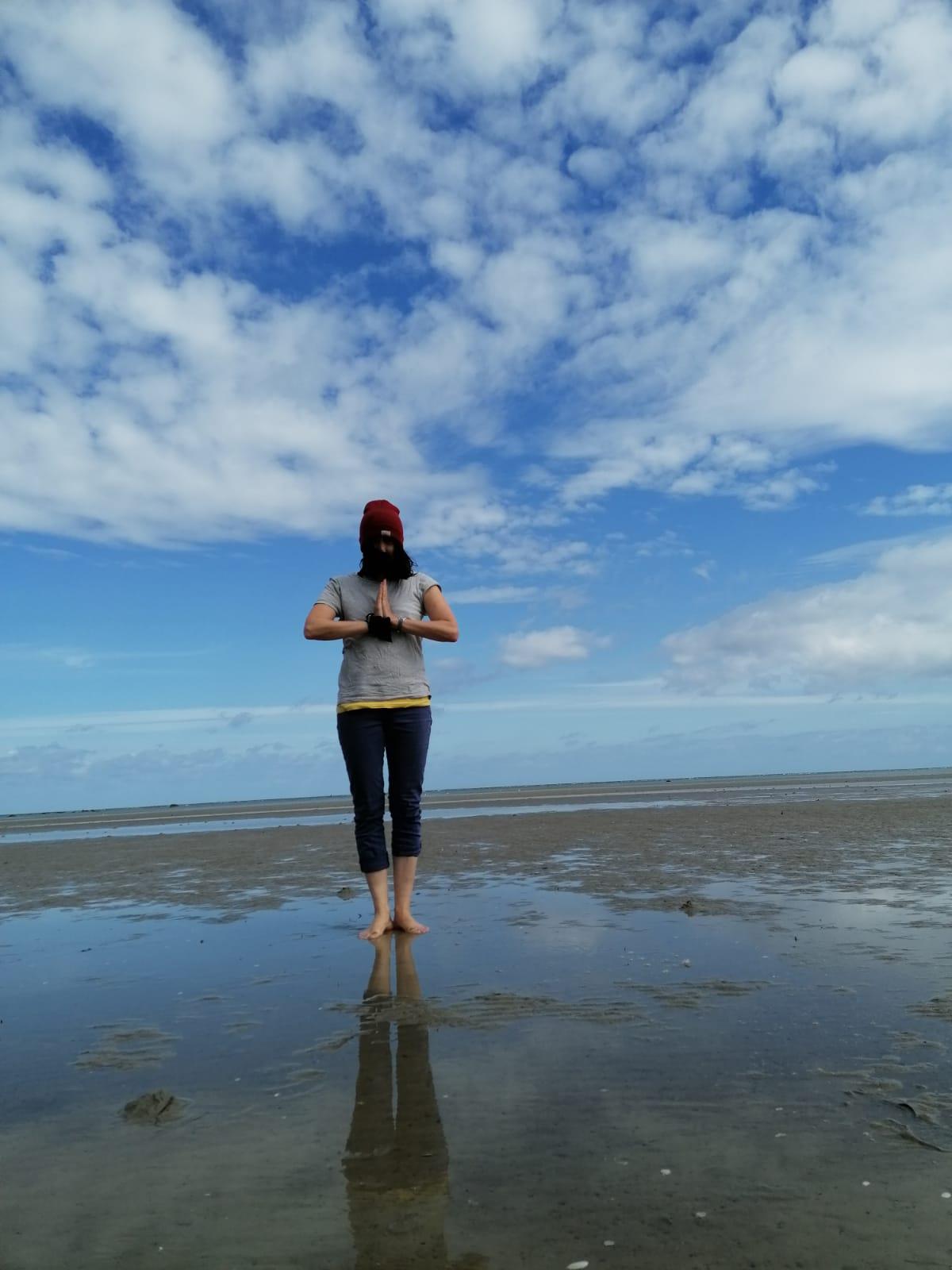 Foto Frau, barfuß am Strand in meditativer Haltung die Hände vor der Brust zusammengelegt, hinter ihr der blaue Himmel