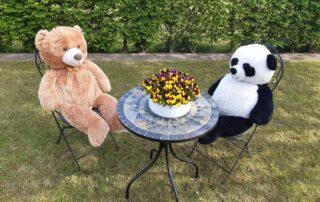 Foto Zwei dicke, große Teddybären sitzen an einem Bistrotisch auf einer Rasenfläche